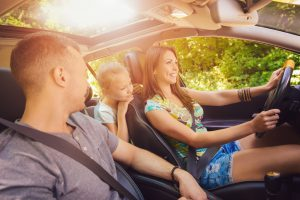 Beautiful family of three enjoying at driving a car and going on road trip.